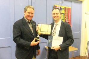 Champion Chris receiving his certificate & trophies from Mark for winning the Club Speech Contest.