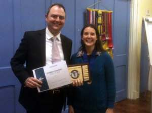 Double-winner of 2015's International Speech & Evaluation Contest Chris Boden, receiving his awards from Club President Julie Farrell.